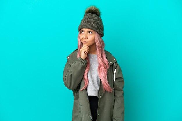 Mulher jovem com cabelo rosa vestindo um casaco à prova de chuva isolado em um fundo azul, tendo dúvidas e pensando