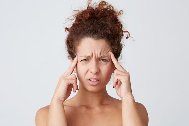 Mulher jovem com cabelo ruivo cacheado e dor de cabeça
