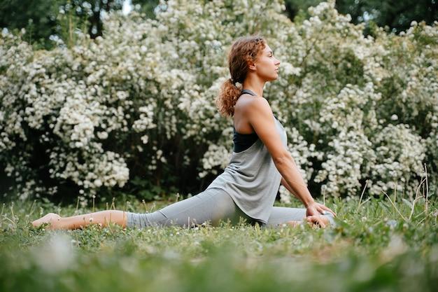 Mulher jovem com cabelo ruivo treina fazendo exercícios em pose de ioga de um piloto ao ar livre no parque