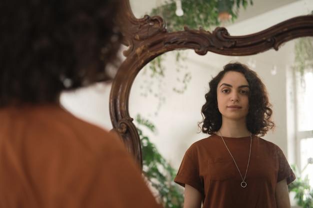 Mulher jovem com cabelos cacheados em frente ao espelho e se olhando