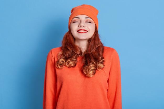 Mulher jovem com cabelos ruivos, fica de olhos fechados, imagina momento agradável