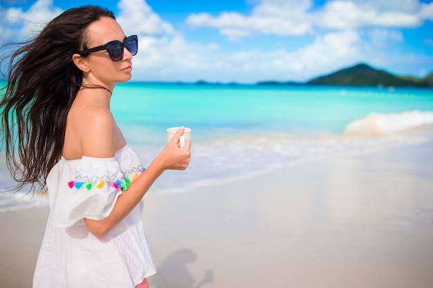 Mulher jovem, com, café quente, desfrutando, vista praia