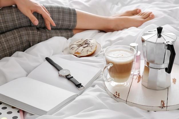 Mulher jovem com café quente sentada na cama de manhã