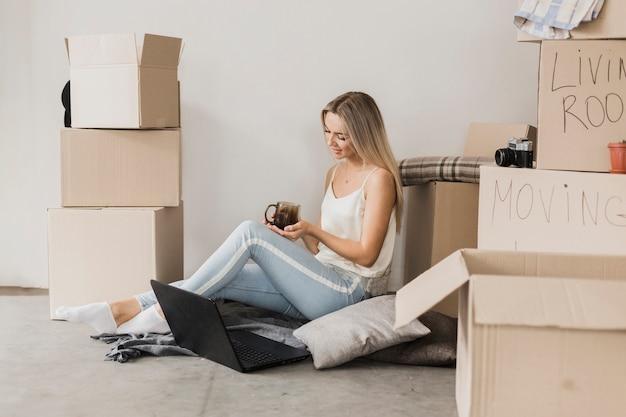 Mulher jovem, com, café, sentar chão