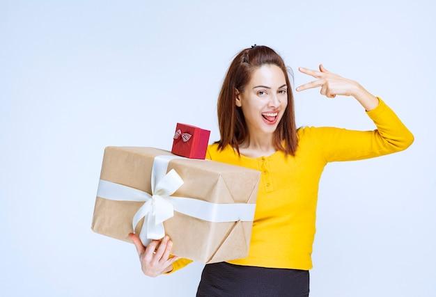 Mulher jovem com camisa amarela segurando uma caixa de presente vermelha e outra de papelão e mostrando um sinal positivo com a mão