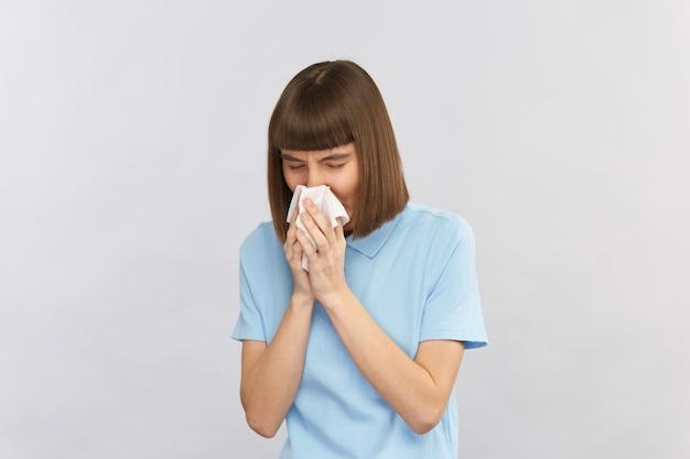 Mulher jovem com camisa azul assoa o nariz em um tecido branco isolado em cinza, copie o espaço