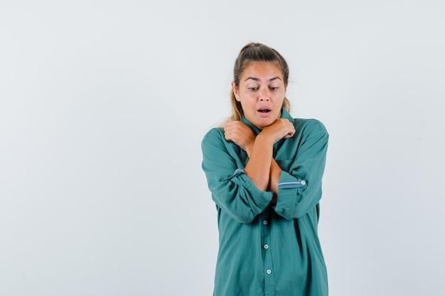 Mulher jovem com camisa azul cruzando as mãos no peito enquanto olha para o chão e parece assustada