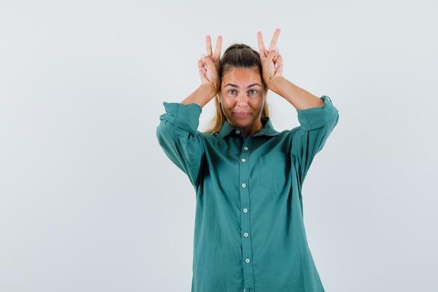 Mulher jovem com camisa azul mostrando o sinal de v na cabeça e parecendo divertida