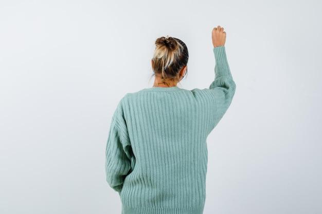 Mulher jovem com camisa branca e casaco de lã verde menta virando-se e fingindo estar escrevendo algo e parecendo focada