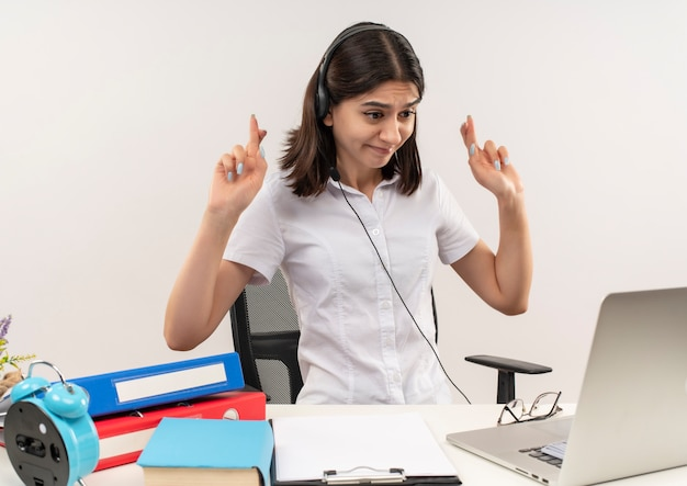 Mulher jovem com camisa branca e fones de ouvido com um microfone sentada à mesa com pastas olhando para a tela do laptop na videochamada fazendo desejável desejo cruzando os dedos sobre a parede branca