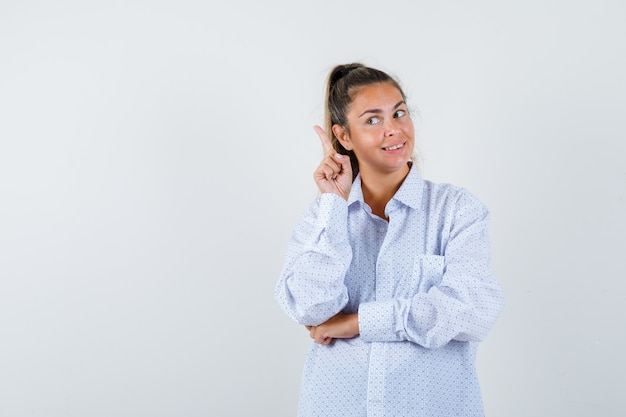 Mulher jovem com camisa branca levantando o dedo indicador em gesto de eureca e parecendo sensata