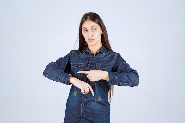 Mulher jovem com camisa jeans apontando para a hora