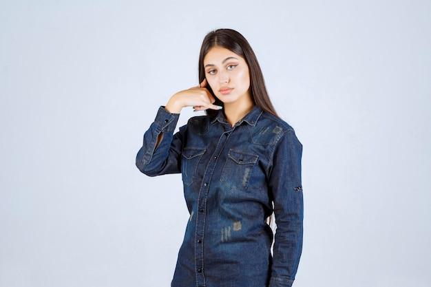 Mulher jovem com camisa jeans mostrando sinal de chamada