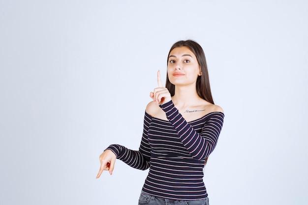 Mulher jovem com camisa listrada apontando para algo atrás