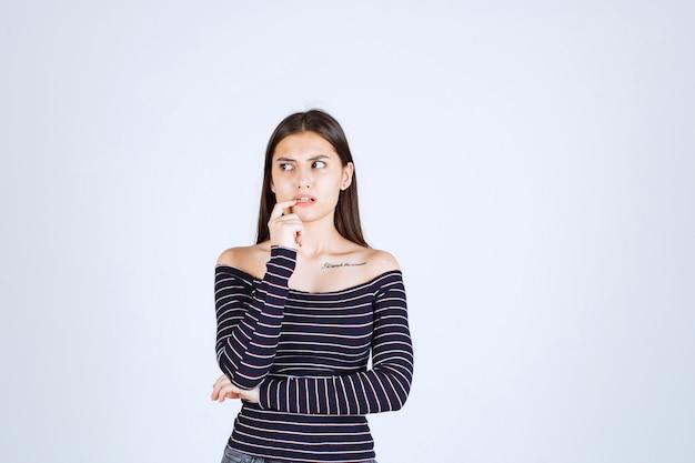 Mulher jovem com camisa listrada colocando a mão no queixo e pensando