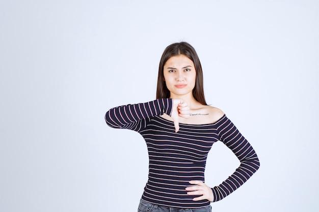 Mulher jovem com camisa listrada mostrando o polegar para baixo