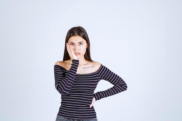 Mulher jovem com camisa listrada, segurando a cabeça por causa da dor de cabeça