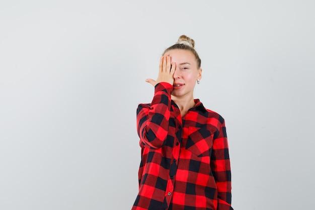 Mulher jovem com camisa xadrez segurando a mão em um olho e parecendo animada