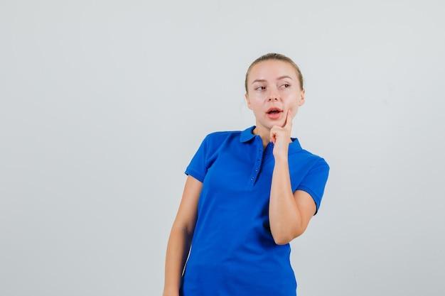 Mulher jovem com camiseta azul olhando para o lado com o dedo na covinha e parecendo pensativa