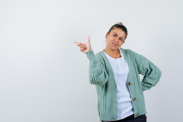 Mulher jovem com camiseta branca e casaquinho verde menta apontando para a esquerda com o dedo indicador, piscando e parecendo atraente