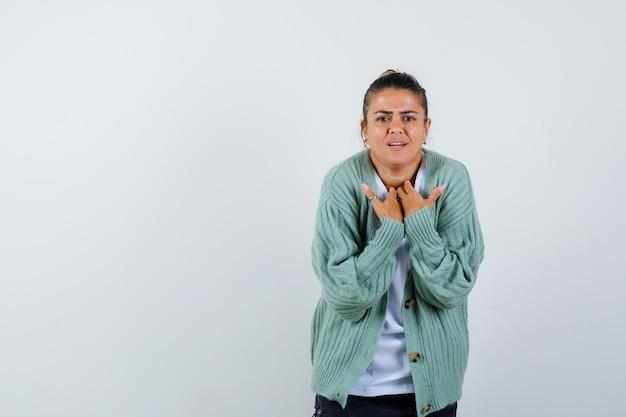 Mulher jovem com camiseta branca e casaquinho verde menta apontando para si mesma e parecendo zangada