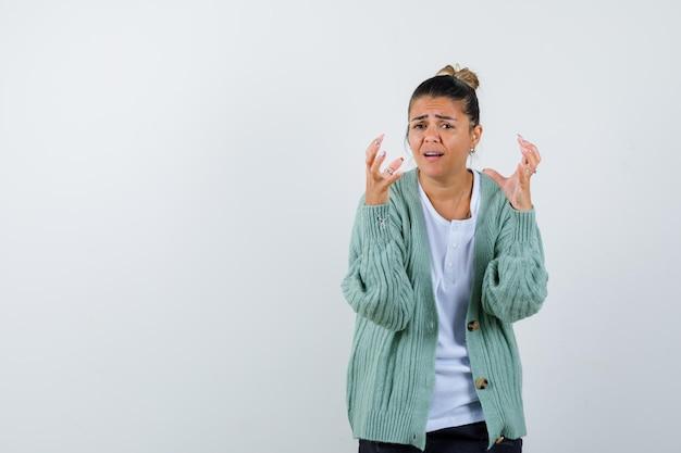 Mulher jovem com camiseta branca e casaquinho verde menta esticando as mãos enquanto segura algo e parecendo irritada