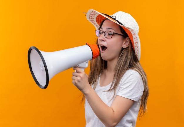 Mulher jovem com camiseta branca e chapéu de verão gritando para o megafone em pé sobre a parede laranja