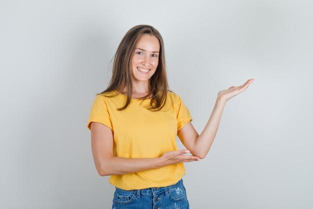 Mulher jovem com camiseta e shorts convidando a vir com as mãos e parecendo alegre