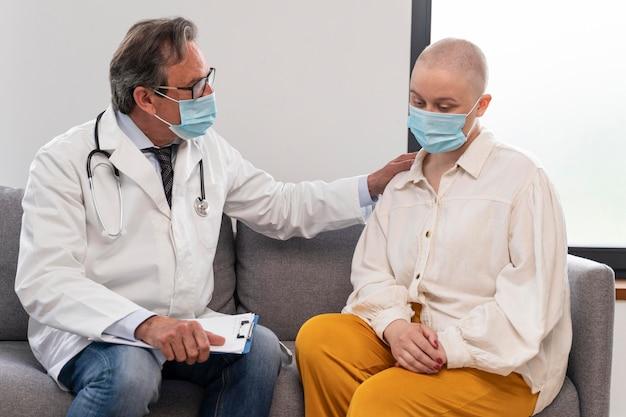 Mulher jovem com câncer de mama conversando com o médico
