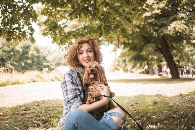 Mulher jovem, com, cão, sentando, parque