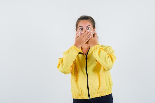 Mulher jovem com capa de chuva amarela de mãos dadas na boca e parecendo assustada