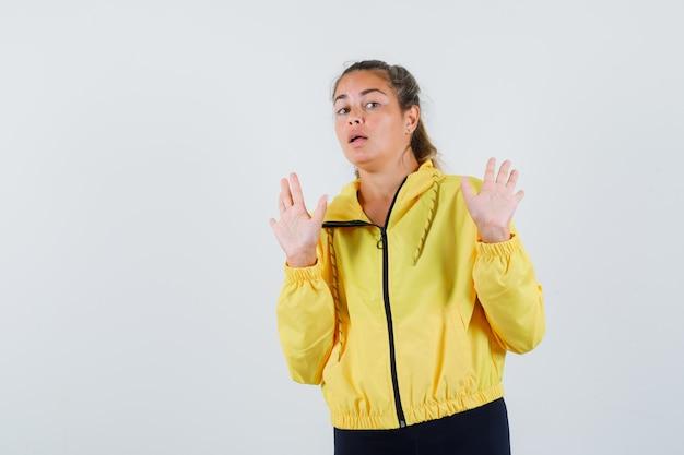 Mulher jovem com capa de chuva amarela levantando as mãos por rejeitar algo e parecendo relutante