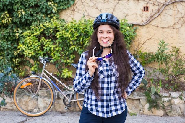 Mulher jovem com capacete tira os óculos de sol no fundo da bicicleta e do beco