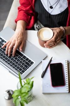 Mulher jovem com cappuccino pressionando as teclas do teclado do laptop enquanto faz networking à mesa no café