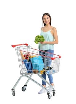 Mulher jovem com carrinho de compras na superfície branca