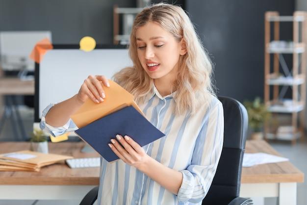 Mulher jovem com cartas no escritório