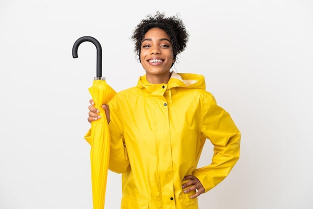 Mulher jovem com casaco à prova de chuva e guarda-chuva isolado no fundo branco, posando com os braços na cintura e sorrindo