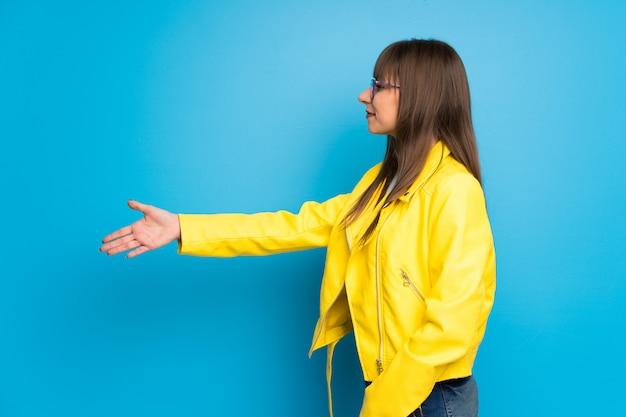 Mulher jovem, com, casaco amarelo, ligado, azul, fundo, handshaking, após, bom negócio