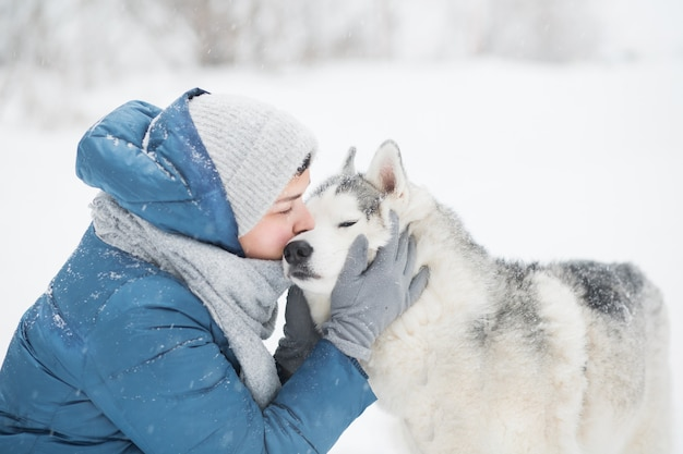 Mulher jovem com casaco azul beijando husky siberiano nevado no inverno