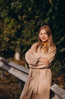 Mulher jovem com casaco bege caminhando no parque
