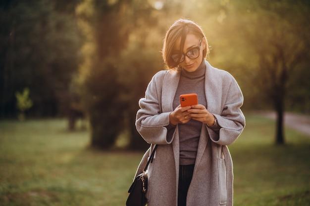 Mulher jovem com casaco cinza falando ao telefone no parque