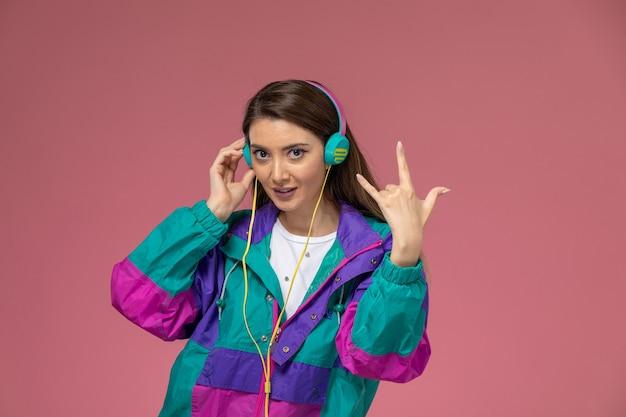 Mulher jovem com casaco colorido, ouvindo música na parede rosa claro de frente, pose de mulher modelo
