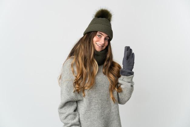 Mulher jovem com chapéu de inverno isolada na parede branca saudando com a mão e expressão feliz