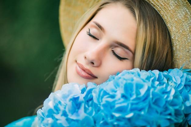 Mulher jovem com chapéu de palha cheira flores de hortênsia azuis caminhando na rua de verão