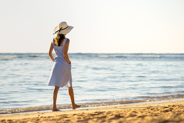 Mulher jovem com chapéu de palha e um vestido andando sozinha na praia de areia vazia na beira-mar