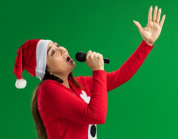 Mulher jovem com chapéu de papai noel de natal e suéter vermelho segurando o microfone cantando feliz e animada com o braço levantado em pé sobre um fundo verde