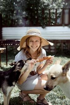 Mulher jovem com chapéu de verão grelhando carne ao ar livre no quintal, sentada com o cachorro, dando um lanche para o animal de estimação