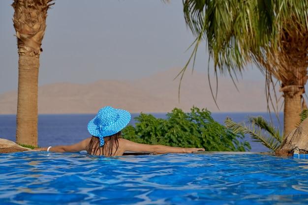 Mulher jovem com chapéu de verão na piscina em uma viagem ao mar e olha o pôr do sol no egito