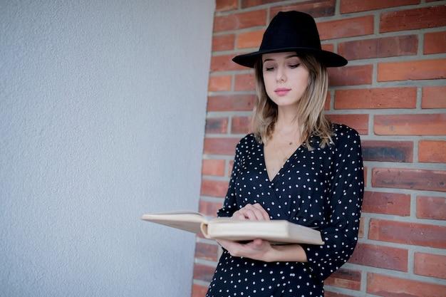Mulher jovem com chapéu e livro na parede de tijolos