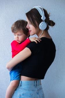 Mulher jovem com chapéu e roupas estilo anos 90 e um filho pequeno na parede branca